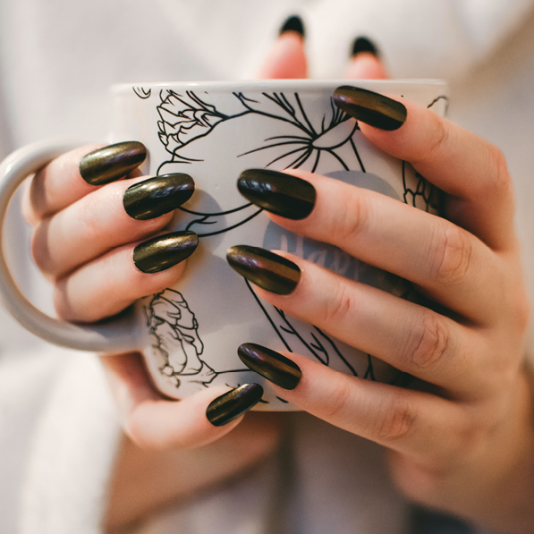 Close up of woman's hands holding a white mug, her nails are long and painted dark