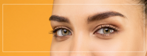 close up of woman's eyes and eyebrows on an orange background